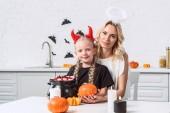 portrét matka a dcera v kostýmech halloween s dýní u stolu s sladkosti v černý hrnec v kuchyni doma
