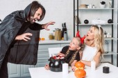 Fotografie portrait of parents and daughter in halloween costumes at table with treats in black pot in kitchen at home
