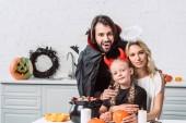portré, a szülők és a lánya halloween jelmez asztalnál kezeli fekete pot otthon a konyhában