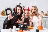 portrét rodičů a dcery v halloween kostýmy u stolu se považuje v černý hrnec v kuchyni doma