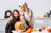 portrét rodiny v halloween kostýmy do dýně společně v kuchyni doma
