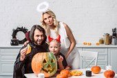 portrait of family in halloween costumes at table with pumpkins in kitchen at home