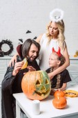 portrét rodiny v halloween kostýmy u stolu s dýně v kuchyni doma