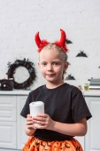 Fotografie portrait of little kid with red devil horns holding candle in hands at home, halloween holiday concept