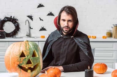 portrait of man in vampire halloween costume sitting at table with pumpkins in kitchen at home
