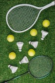 Photo top view of badminton and tennis equipment arranged on green lawn