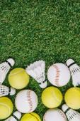 Photo top view of arrangement of badminton shuttlecocks, tennis and baseball balls on green lawn