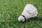 Fotografie close up view of white shuttlecock lying on green lawn