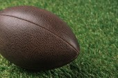 close up view of leather rugby ball lying on green grass