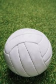 Fotografie close up view of white volleyball ball on green grass