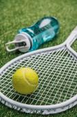 zblízka pohled tenisové vybavení a sportovní láhev s vodou na zelené trávě