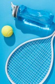 close up view of sportive water bottle and tennis equipment on blue backdrop