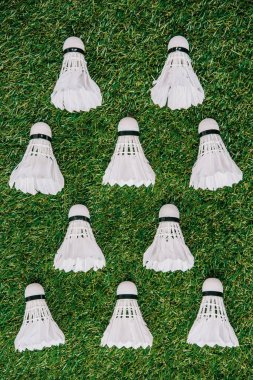 top view of white shuttlecocks arranged on green grass