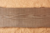 Photo top view of wooden plank on crumpled paper backdrop