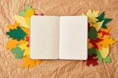 top view of empty notebook and colorful handmade paper leaves on crumpled paper backdrop