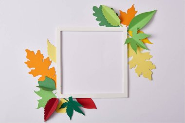 flat lay with handcrafted paper leaves and empty frame on white tabletop
