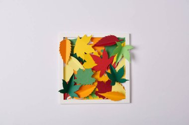 flat lay with handcrafted paper leaves and frame on white tabletop