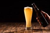 a férfi csengő sörösüveg részleges kilátással bögre friss sör: fából készült asztal
