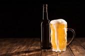 pivo s pěnou odtéká a láhev piva na dřevěný stůl, minimalistické pojetí