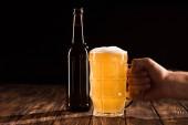 Fotografia immagine potata della tazza tintinnio uomo con bottiglia di birra al tavolo di legno