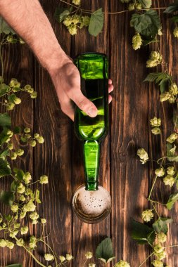 cropped image of man pouring beer into glass at wooden table with hop