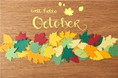 top view of colorful papercrafted foliage with well hello october lettering on wooden background