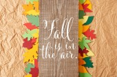 Fotografie top view of wooden plank with fall is in the air inspiration and colorful paper leaves arrangement on crumpled paper backdrop