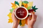 Fotografie Teilansicht einer Frau mit heißem Tee und Willkommen im Herbst -Schriftzug auf bunten Blättern