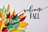 flat lay with colorful handmade paper foliage arranged on white background with welcome fall inspiration