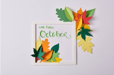 flat lay with handcrafted paper leaves and white frame with