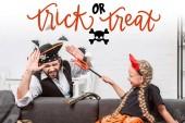 Fotografia Ritratto della figlia e del padre in costumi di halloween che gioca in casa con dolcetto o scherzetto lettering