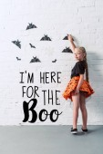 back view of child in skirt hanging black paper bats on white brick wall, halloween holiday concept with Im here for the Boo lettering