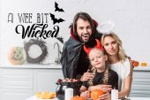 portré, a szülők és a lánya halloween jelmez kezeli a konyha otthon egy icipicit gonosz betűk fekete kasszát az asztalnál