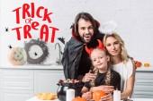 portré, a szülők és a lánya halloween jelmez asztalnál kezeli fekete pot a konyha otthon fogás vagy élvezet felirat