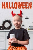 portrait of little kid with red devil horns holding candle in hands at home, with halloween lettering
