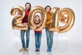 šťastní rodiče s dcerou drží podepsat 2019 z zlaté balónky pro nový rok izolovaných na bílém pozadí