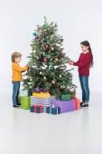 Fotografie sourozenci, zdobí vánoční stromeček s dárky, izolované na bílém