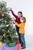 Fotografie Happy sourozenci, zdobí vánoční stromeček s dárky, izolované na bílém