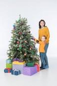 Fotografie lächelnde Mutter mit Sohn schmücken Weihnachtsbaum mit präsentiert isoliert auf weiss