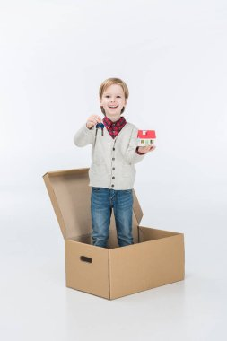 Little boy holding carton house and key from new house ready to move into new house isolated on white