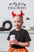 portrait of little kid with red devil horns holding candle in hands at home, with my first halloween lettering