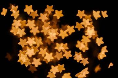 Full frame of golden stars bokeh lights on black background stock vector