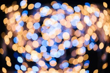 full frame of blue and golden defocused bokeh lights on black background