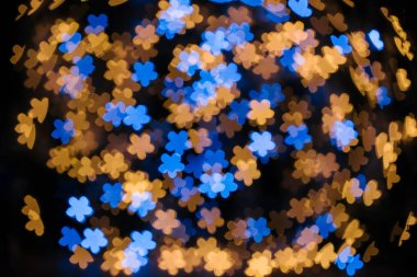 full frame of shiny blue and golden stars bokeh lights on black backdrop