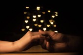 cropped shot of couple holding hands with hearts bokeh background