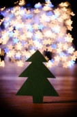 close up view of green paper christmas tree on wooden tabletop and bokeh lights in shape of stars background