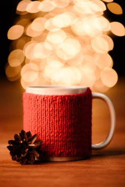 Close up view of cup of hot drink and pine cone on wooden tabletop with bokeh lights  background stock vector