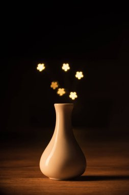Close up view of white vase and yellow stars bokeh lights on black background stock vector