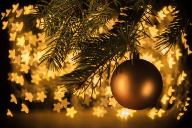 close up view of golden christmas ball hanging on pine tree with stars bokeh lights background
