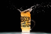 Photo mug of light  beer with foam and splashes at table on black background with beer with the friends inspiration